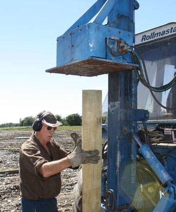John Weatherall holds a post ready to be pressed into the soil.