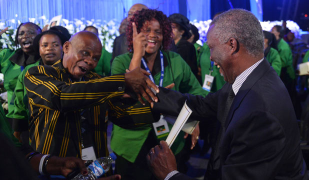 Former South African President Thabo Mbeki, right, is greeted by African National Congress supporters attending the funeral ceremony of former South African