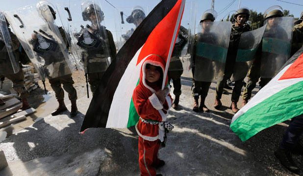 A boy holds a Palestinian flag as he stands in front of Israeli soldiers at the controversial Israeli barrier in the West Bank village of al-Masara near Bethlehem.