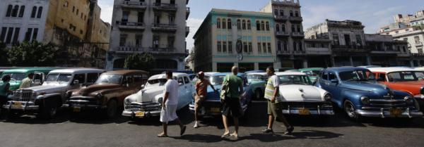 Drivers wait for customers beside their US-made cars at a private collective taxi stand in Havana.
