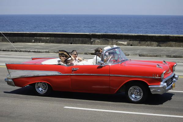 Tourists ride a US-made 1957 Chevrolet Bel-Air convertible car on Havana's seafront boulevard