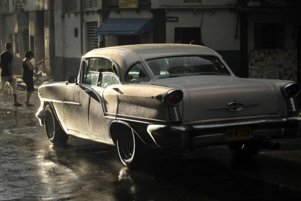 People cross a street as a US-made car, used as a private collective taxi is driven as it rains in Havana September 30, 2013.