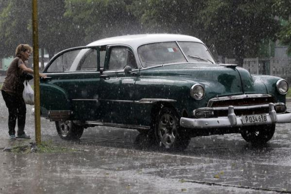 A woman exits a US-made car, used as a private collective taxi during a heavy thunderstorm in Havana September 30, 2013. Collective taxis have established routes aro