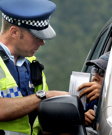 Highway patrol constable Dwight Grieve writes out a ticket for a Chinese national