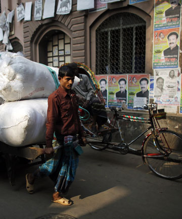 A worker pulls a cart past posters of Bangladesh electoral candidates