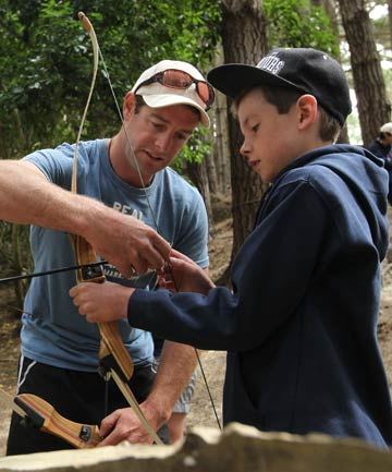 GETTING INVOLVED: Mark Ludemann, a Camp Quality companion, shows 10-year-old Luke Tanner, who is recovering from cancer, how to use a bow at the annual summer camp at Governors Bay.
