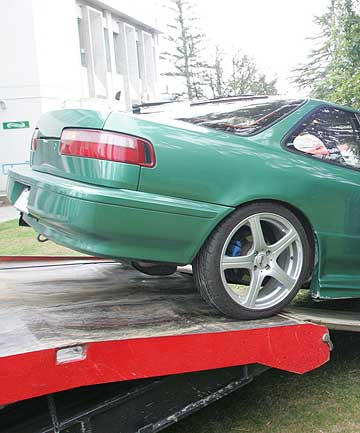 A confiscated car is loaded onto a trailer.