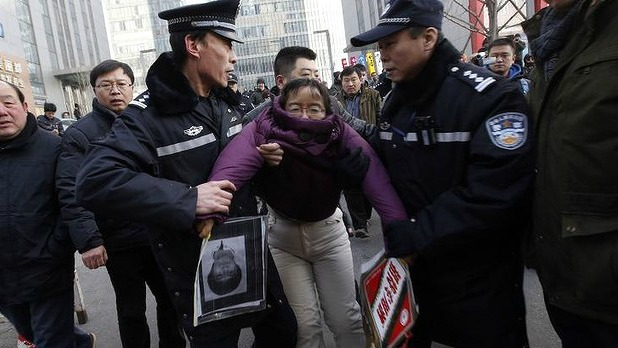 A supporter of Xu Zhiyong is detained by policemen near the court.