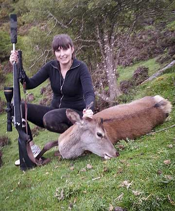 Fairfax Media reporter Kelsey Fletcher stands over a deer she shot in the Pohangina Valley.