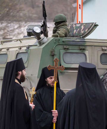 Orthodox monks next to an armed serviceman in a Russian army vehicle outside a Ukrainian border guard post