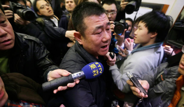 A relative of a passenger of Malaysia Airlines flight MH370 speaks to journalists at a hotel in Beijing