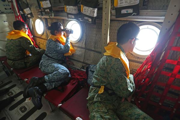 Military personnel look out of a Singapore Air Force plane during the search