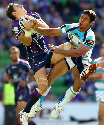 Billy Slater of the Storm catches the ball in front of Albert Kelly of the Titans
