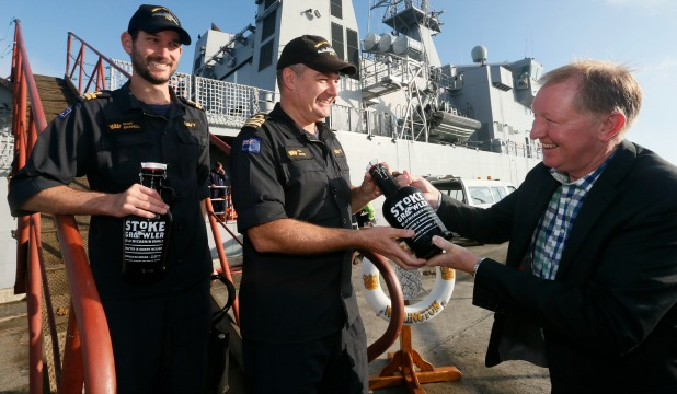 Nick Smith, right, hands some  beer to Phil Rowe, centre, commander of HMNZS Wellington and executive officer Grant Bicknell.