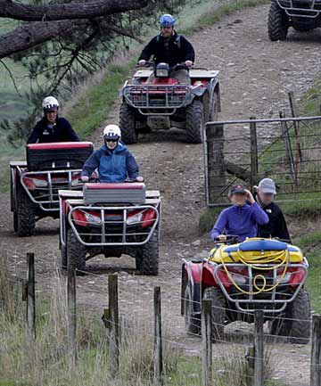 Some quad bike operators wear helmets, another doesn't and carries an unhelmeted passenger a farming field day in Manawatu recently.