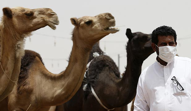 A man wearing a mask poses with camels at a market in the village of al-Thamama near Riyadh.