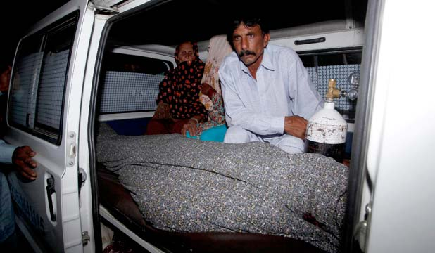 Mohammad Iqbal sits next to his wife Farzana's body