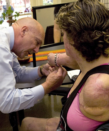 Don Dobrow places braclets on his daughter, Kaitlyn Dobrow, after a therapy sesssion in Downey, Calif.