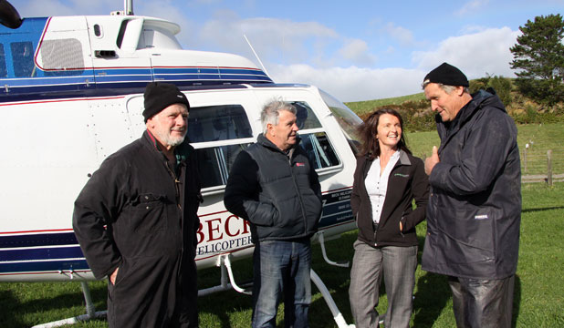 Farmers Brian Schumacher, left, and Ian Jury, right, talk to helicopter pilot Alan Beck and Taranaki Federated Farmers president Bronwyn Muir about removing wires from  farms.