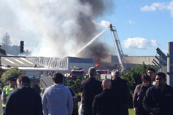Firefighters battle the blaze in a bitumen tank next to a building at the Thermakraft premises.
