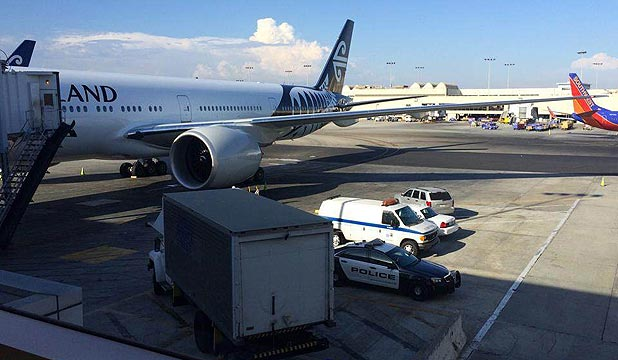 DEATH ON PLANE: A coroner's van is parked outside the Air New Zealand Boeing 777 jet in Los Angeles.