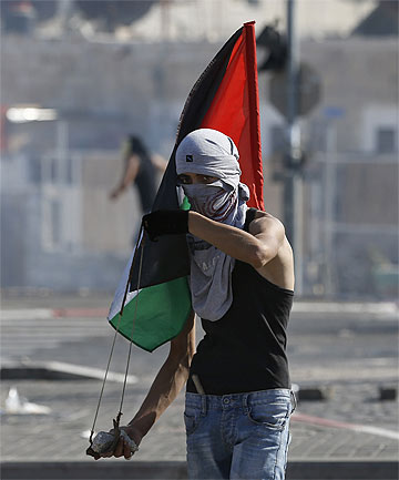 PROTESTS: A Palestinian youth holds a Palestinian flag and and a sling during clashes with Israeli police.