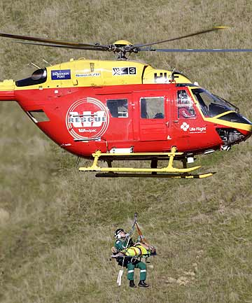 CRASH: The Westpac rescue helicopter winches the second hunter up from the site of the crash.