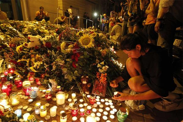 People bring flowers and candles to the Dutch embassy to commemorate the victims of the Malaysia Airlines plane crash.
