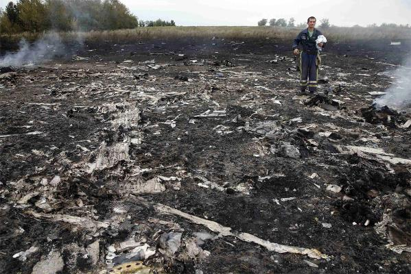 An Emergencies Ministry member walks at the site of the Malaysia Airlines plane crash.