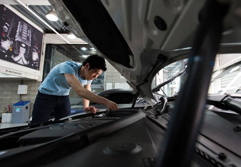 An employee works on a customised BMW 1 Series 118d vehicle at a Seoul garage.