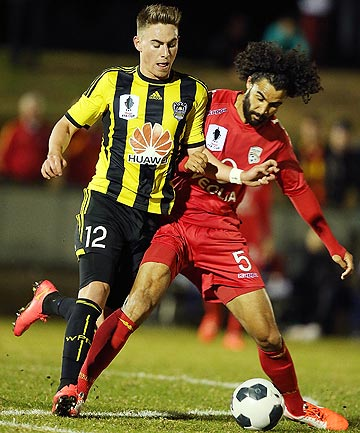 TIGHT TUSSLE: Phoenix player Tyler Boyd and Adelaide United's Osama Malik contest possession in their opening round FFA Cup fixture.