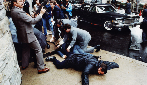 ile photo showing the moments just after John Hinckley tried to assassinate former U.S. President Ronald Reagan on March 30, 1981 outside the Washington Hilton hotel. A Secret Service agent (L) draws his Uzi sub-machine gun as others subdue Hinckley behind him.