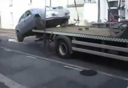 Motorist incensed with a having his car towed jumps into it, reverses off a tow truck and drives it away.