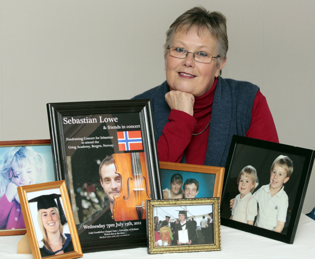Maria Lowe with photos of her two homeschooled children who are now grown up