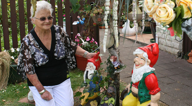 DISGRACEFUL THEFT: Colleen Cheak with some of her remaining gnomes after many were taken from her property.