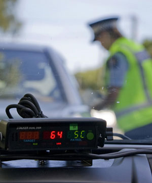NABBED: Constable Nicola Laurenson tickets a driver for driving at 64kmh in Linwood Ave in a 50kmh zone yesterday.