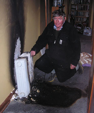 OVERHEATED: Ohai man Peter Templer viewing the damage done to his house by an exploding oil column heater.