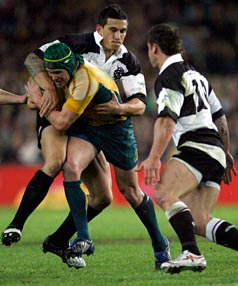 HOLD ON: Australia's Matt Giteau is tackled by Barbarians' Sonny Bill Williams while Luke McAlister prepares to weigh in.