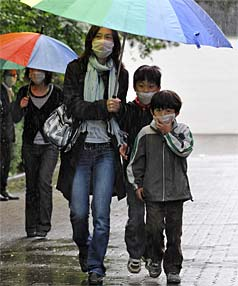 FLU ZONE: School children and parents wear face masks as they leave the Japanese International School in Germany. Authorities have confirmed 30 cases of the H1N1 flu at the school.