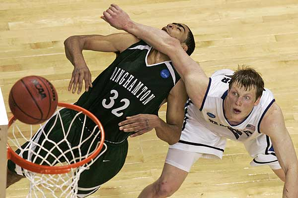 Duke University forward Kyle Singler (12) blocks out Binghamton University guard Emanuel Mayben (32) during the first round of the NCAA college basketball tournament at the Greensboro Coliseum in Greensboro, North Carolina.