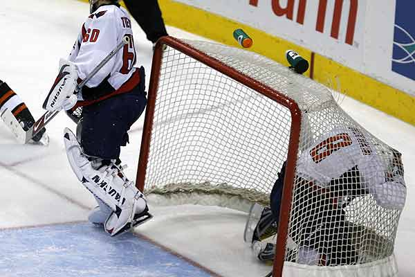 Washington Capitals winger Alex Ovechkin (right) knocks the net from its mount behind Capitals goalie Jose Theodore while playing against the Philadelphia Flyers during the third period of their NHL hockey game in Philadelphia, Pennsylvania.