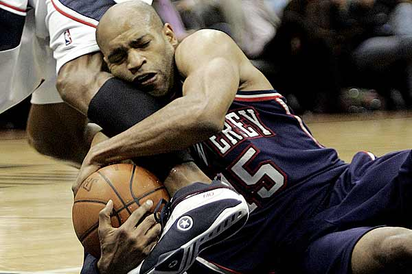 New Jersey Nets guard Vince Carter grabs a loose ball and the leg of Atlanta Hawks guard Maurice Evans in the second half of NBA basketball action in Atlanta, Georgia.