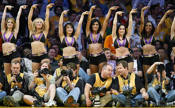 Los Angeles Laker Girls perform behind photographers on the sidelines during Game 2 of the NBA Finals between the Los Angeles Lakers and the Orlando Magic in Los Angeles.