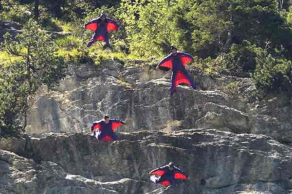 Base jumpers leap from a alpine cliff in the Lauterbrunnen valley in the Bernese Oberland, Switzerland.