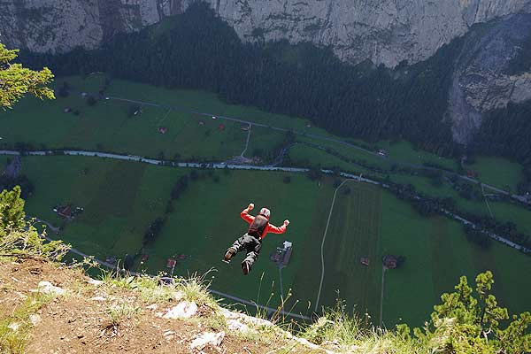 Base jumper Martin Schuermann leaps from a alpine cliff in the Lauterbrunnen valley in the Bernese Oberland, Switzerland.