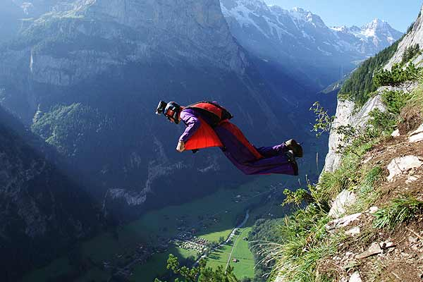 A base jumper leaps from a alpine cliff in the Lauterbrunnen valley in the Bernese Oberland, Switzerland.