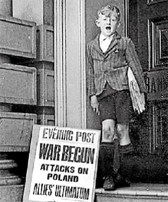 READ ALL ABOUT IT! A newspaper boy with a billboard headlining the beginning of World War II.