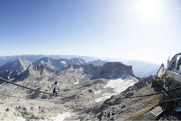 Freddy Nock from Switzerland balances on the ropeway of a cable car leading on Germany's highest mountain, the 2962 metre Zugspitze in front of the panorama of the Alps, near the southern Bavarian resort of Garmisch-Partenkirchen.