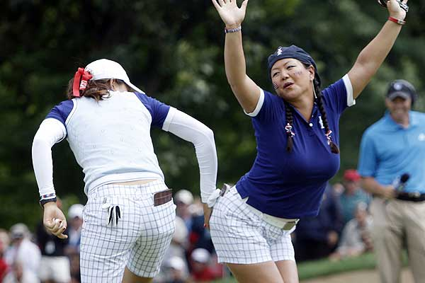 Christina Kim (right) and Michelle Wie (left) of the US celebrate after winning their fourballs match on the second day of the 2009 Solheim Cup golf tournament at Rich Harvest Farm in Sugar Grove, Illinois.