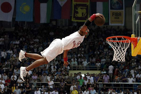A Chinese performer soars through the air as he slams a basketball into the basket during a show at half-time during the final of the Asian Basketball Championships between China and Iran in Tianjin.